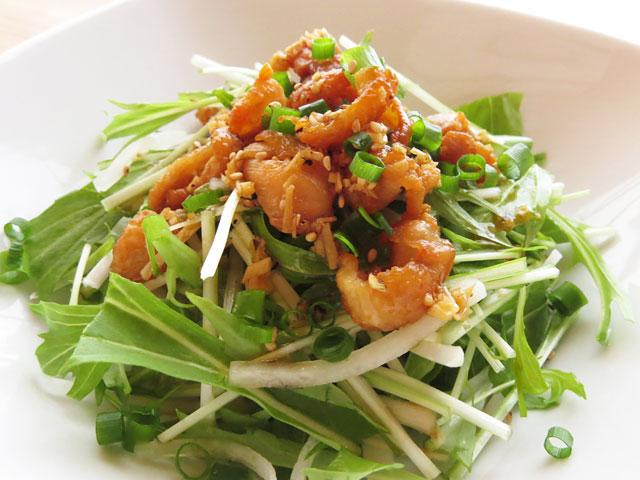 白いお皿に盛られた鶏皮揚げと水菜と大根のサラダ